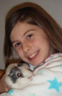 Girl holding guinea pig in her arms